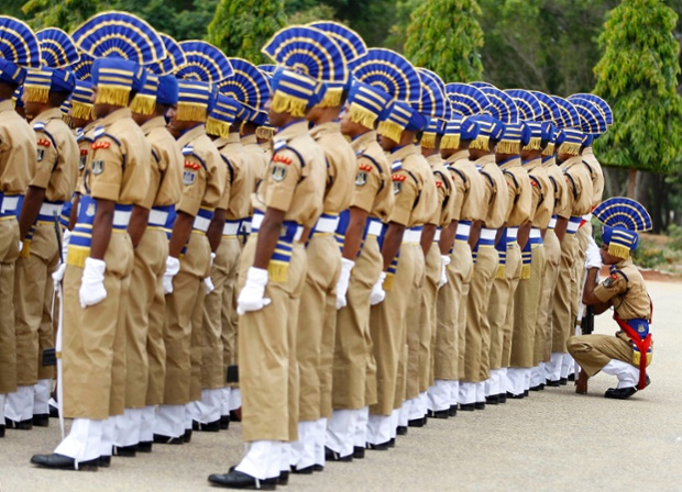 An Indian Central Reserve Police Force (CRPF) soldier takes a break behind his fellow soldiers during their passing-out parade in Bangalore, India. Presumably he doesn't want to literally pass out.