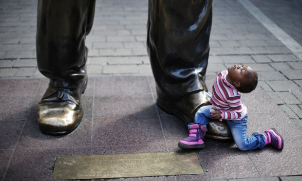 Little Ndzelo looks up..and up... to the six metre tall sculpture of former South African President Nelson Mandela as she plays at the foot of the statue in Nelson Mandela Square, Johannesburg. Latest reports say that Mandela, who was admitted to hospital with a recurring lung infection, is breathing with the help of a respirator.