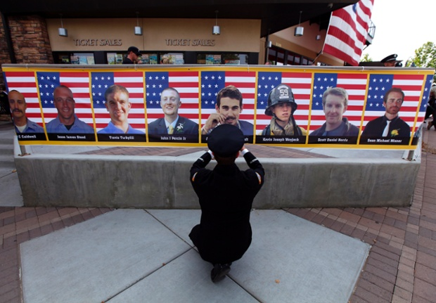 San Diego firefighter Robert Bunsoldat takes a picture of each of the Prescott Fire Department's Granite Mountain Hotshots team from a banner that circles the entrance to their memorial in Prescott Valley, Arizona. Nineteen firefighers lost their lives when they became trapped and their position was overrun by flames from the Yarnell Hill Fire, southwest of Prescott on June 30. Photograph: Mike Blake/Reuters