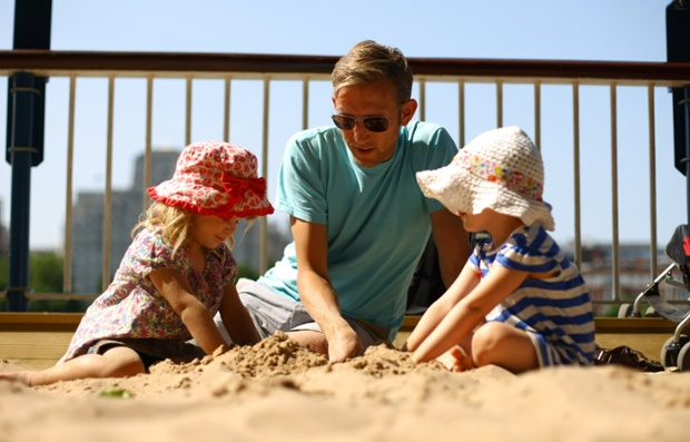 Summertime: A man plays in the sand with his two daughters at the Southbank in London, England. The Met Office has predicted that Britain's current warm weather spell is set to continue into the weekend and beyond.
