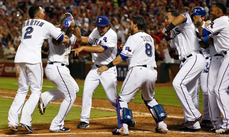 Texas Rangers' Adrian Beltre, left, tosses his helmet to teammate Leonys Martin after hitting the game-winning home run against the Los Angeles Angels on Wednesday.