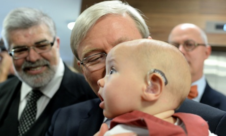 Prime Minister Kevin Rudd holds 5 month old Patrick Wilkinson, who has cochlear implants, during a visit to the hearing hub at Macquarie University in the electorate of Bennelong Monday, Aug. 12, 2013.