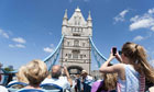 Tourists photograph Tower Bridge