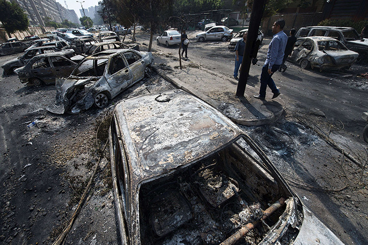Egypt after crackdown: Egyptians pass burnt cars outside the destroyed camp