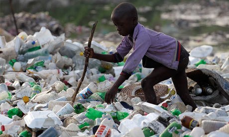 A boy searches through plastic rubbish in a sewage canal for items to sell in Port-au-Prince, Haiti
