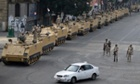 Egyptian army soldiers take their positions on top and next to their armored vehicles while guarding an entrance to Tahrir square, in Cairo, Egypt, Friday, Aug. 16, 2013. (AP Photo/Hassan Ammar)