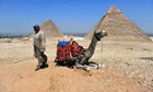 A man waits to offer tourists camel rides at the pyramids in Giza