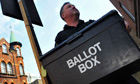 A member of an electoral services team delivers a ballot box to a polling station in London