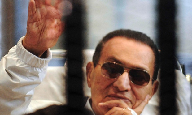 Former Egyptian President Hosni Mubarak waves to his supporters inside a cage in a courtroom at the police academy in Cairo, in this file picture taken April 13, 2013. REUTERS/Stringer/Files