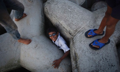 A boy reacts as he is found while playing hide-and-seek under tetrapods on a beach along the Arabian Sea in Mumbai.