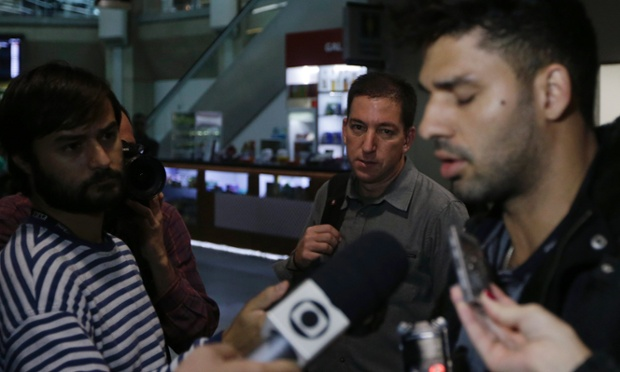 Glenn Greenwald (centre) looks on as his partner David Miranda (right) talks with the media after arriving at Rio de Janeiro's international airport following his detention at Heathrow.