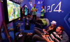 Visitors using Playstation 4s at the Sony exhibition stand during Gamescom 2013 in Cologne.