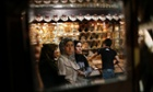 Syrians reflected in a mirror as they shop at the popular Hamidiyeh old market in Damascus.