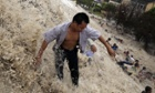 Tourists are washed away by a tidal bore of the Qiantang River
