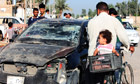 Residents pass by a damaged vehicle in Baquba