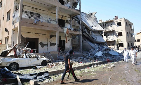 A Syrian fighter walks past damaged buildings at a site activists say was targetted with a car bomb in Raqqa province.