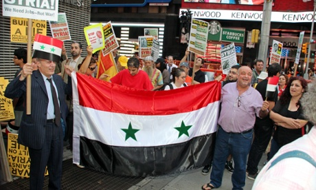 Anti war protesters carry the Syrian flag as they stand near the US Armed Forces Recruiting Center in New York.