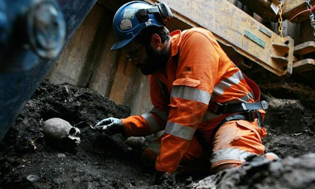 An archaeologist unearths a human skull at the Crossrail building site at London's Liverpool Street
