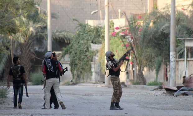 A rebel fighter points his weapon at regime forces in an industrial area of Syria's eastern town of Deir Ezzor.