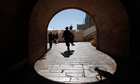 A cat walks behind a man in Jerusalem's Old City