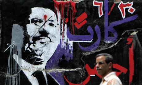 A man walks past graffiti of ousted Egyptian president Mohamed Morsi in central Cairo