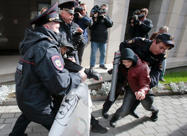 Policemen detain gay rights activists protesting in Moscow against a ban on staging a gay pride parade during the Sochi 2014 Winter Olympic Games.