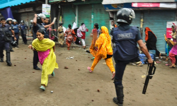Bangladeshi garment workers run as police disperse them during a protest march in Narayanganj, near Dhaka. Protests by workers demanding higher wages entered the fifth day forcing authorities to close more than 100 factories for the day.