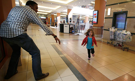 A child runs towards Abdul Yusuf Haji amid a shooting spree at Westgate shopping centre in Nairobi
