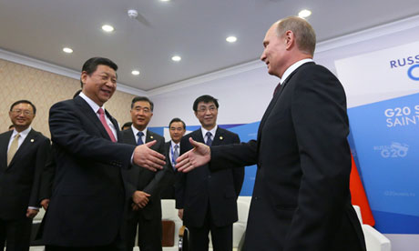 Vladimir Putin shakes hands with Xi Jinping at a meeting at the G20 summit