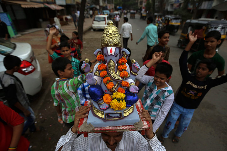 Hindu God Ganesha : A statue decorated with colourful flowers