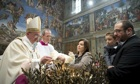 Pope Francis baptises a child in the Sistine Chapel in Rome