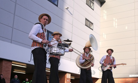 A band on stilts perform outside a football ground. But where?