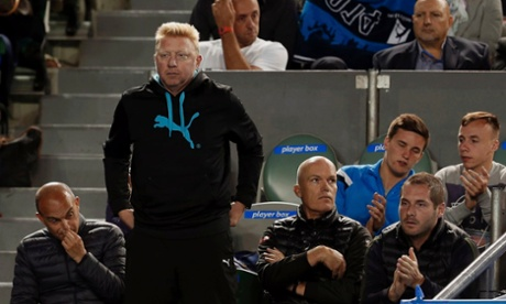 Boris Becker (front row, 2nd L) of Germany, coach of Novak Djokovic of Serbia, stands up as he watches his men's singles quarter-final match against Stanislas Wawrinka of Switzerland at the Australian Open