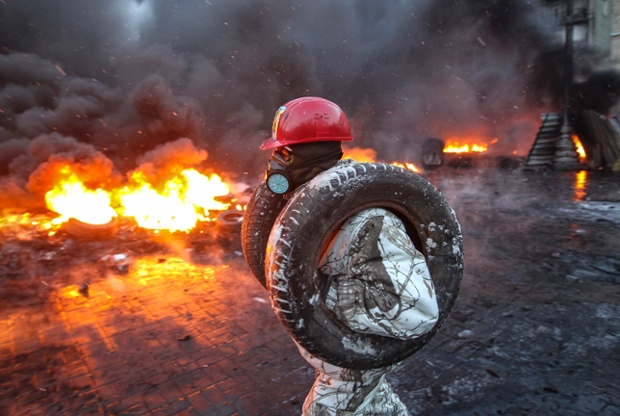 A pro-European integration protester carries tyres to burn at the site of clashes with riot police in Kiev.