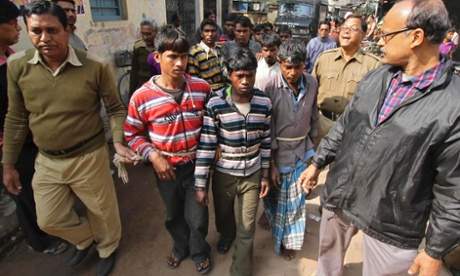 Indian police personnel escort men who are accused of a gang-rape to a court at Birbhum, India.