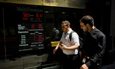 People walk by a sign showing the plunging rate between the Argentine peso and the US dollar in Buenos Aires. The currency has fallen just over 17 percent in the last two days against the dollar, and economic analysts expect inflation to hit 30 percent this year.
