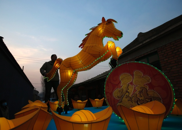 A worker tests the lights in a horse-shaped lantern  at a lantern factory in Beijing.