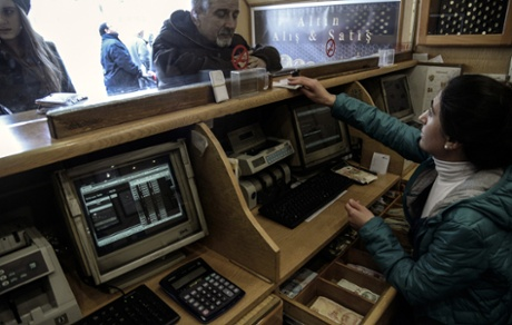 A clerk serves a customer at a currency exchange office in Istanbul on January 23, 2014.