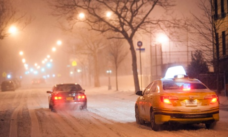 A taxi cab and a few other cars slowly make their way through heavy drizzle on snow-covered streets in Brooklyn, New York, USA, 3 January 2014.
