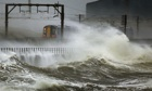 A train passes through storm waves at Saltcoats in Scotland