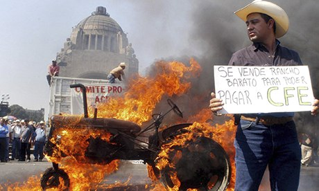 Mexican tractor drivers burn a tyre of one of their vehicles in Mexico City on 31 January 2008 prior to a rally against