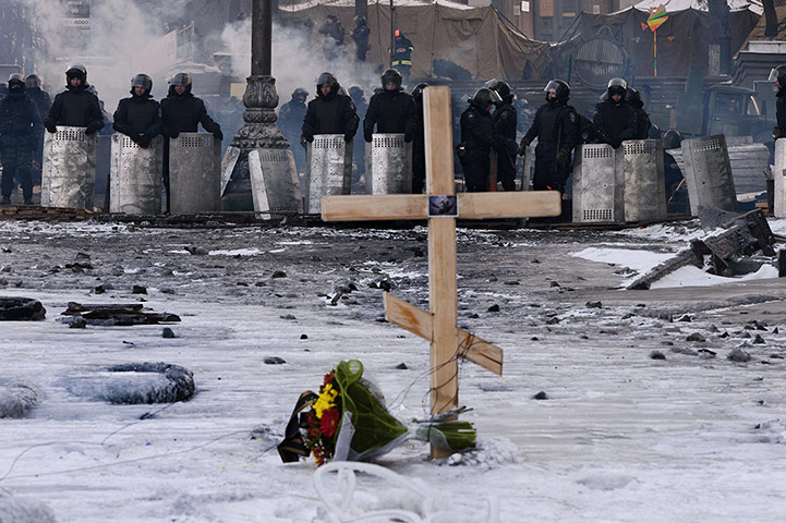 20 Photos: A cross is placed in front of riot policemen at a road block in Kiev