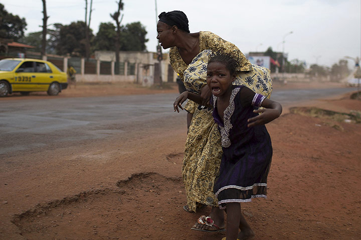 20 Photos: A mother holds her child while attempting to take cover in Bangui
