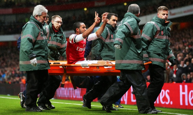 Arsenal's Theo Walcott reminds Tottenham's fans what the score is as he is stretchered off in the second half of the team's FA Cup third-round tie.