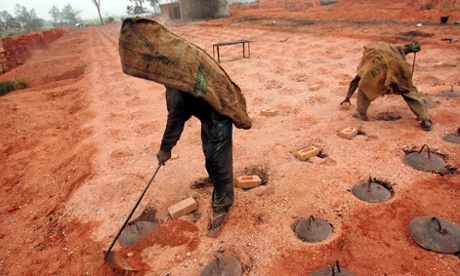 Workers stand on the kilns after closing the opening of a brick kiln and throwing firewood inside.