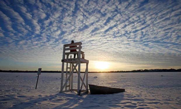 Jennifer Berry watches the sunset from a lifeguard chair over a frozen Lake Calhoun, Minneapolis.