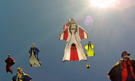 A flock of wingsuit flyers descend toward the Earth