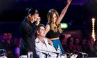 Grinning Melanie Brown and Cheryl Fernandez-Versini standing next to a seated Simon Cowell