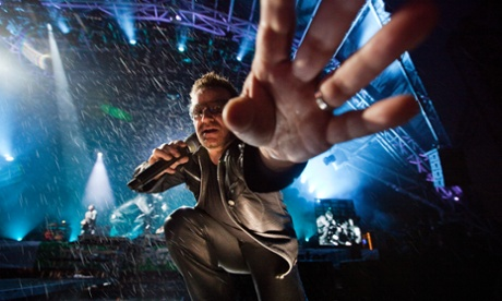 Bono reaches out to take a camera while wearing leather trousers at Glastonbury.