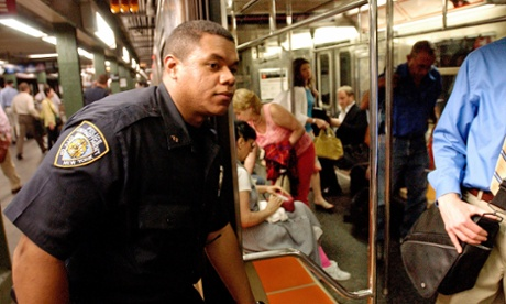 A NYPD officer looks into a train as he patrols the Times Square subway station in New York police